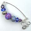 fibula pin, featuring contemporary lampwork beads, fabricated by Robin Atkins, bead artist